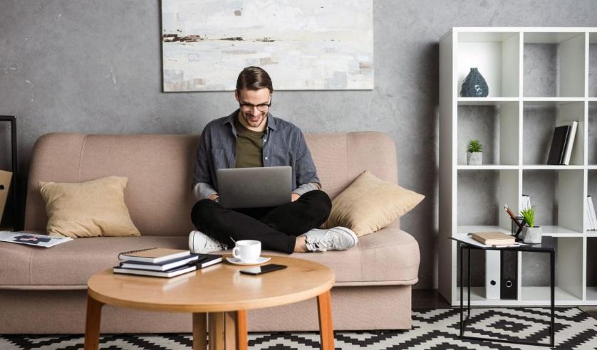 Homme dans son salon avec son ordinateur