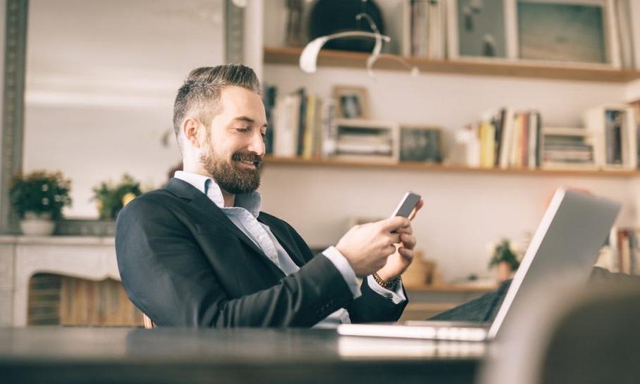 Homme devant telephone et ordinateur
