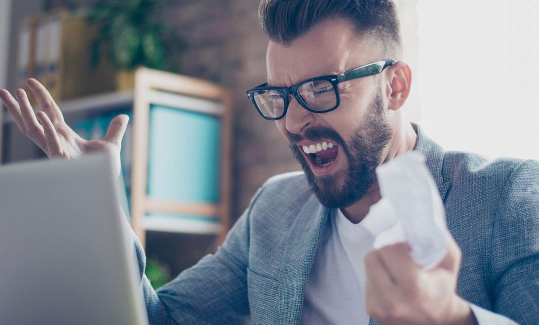 Homme énervé devant son ordinateur