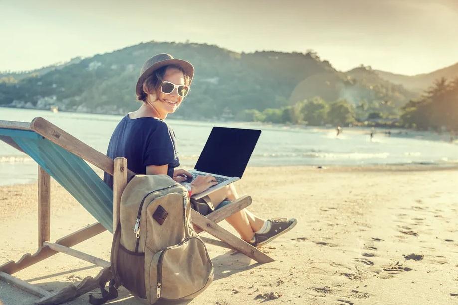 Femme à la plage avec un ordinateur portable