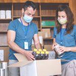 Un homme et une femme en mission humanitaire pour distribuer de la nourriture