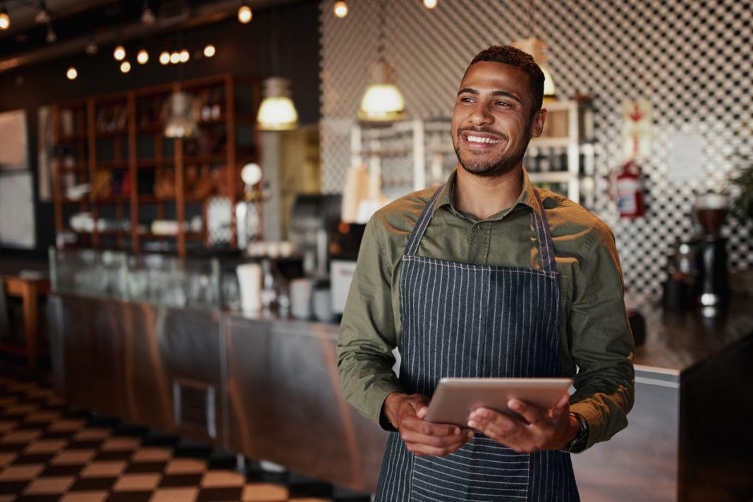 Un homme avec un tablier devant le bar de son restaurant avec une tablette