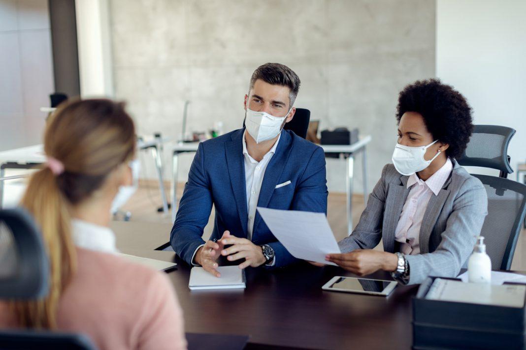Deux personnes entrain de faire passer un entretien à une femme avec les masques