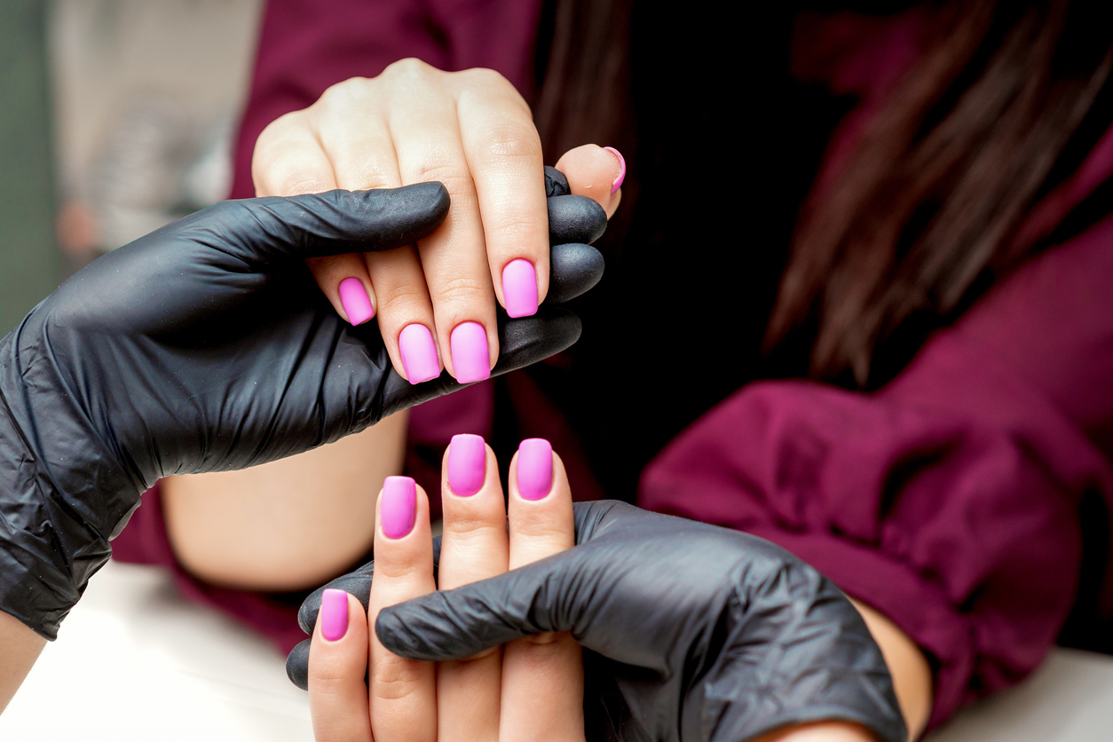 Une prothésiste ongulaire tenant les mains de sa cliente avec du vernis rose