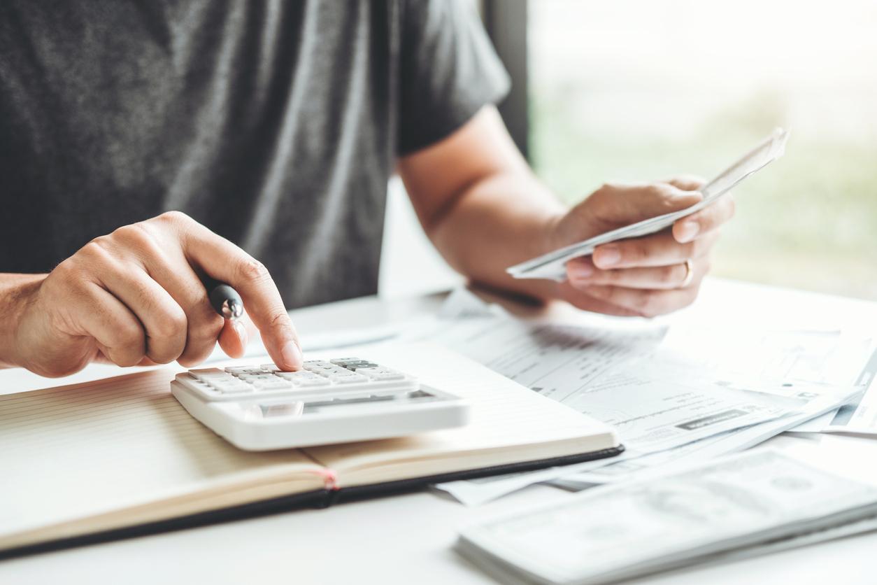 Des mains d'homme avec des papiers et une calculatrice