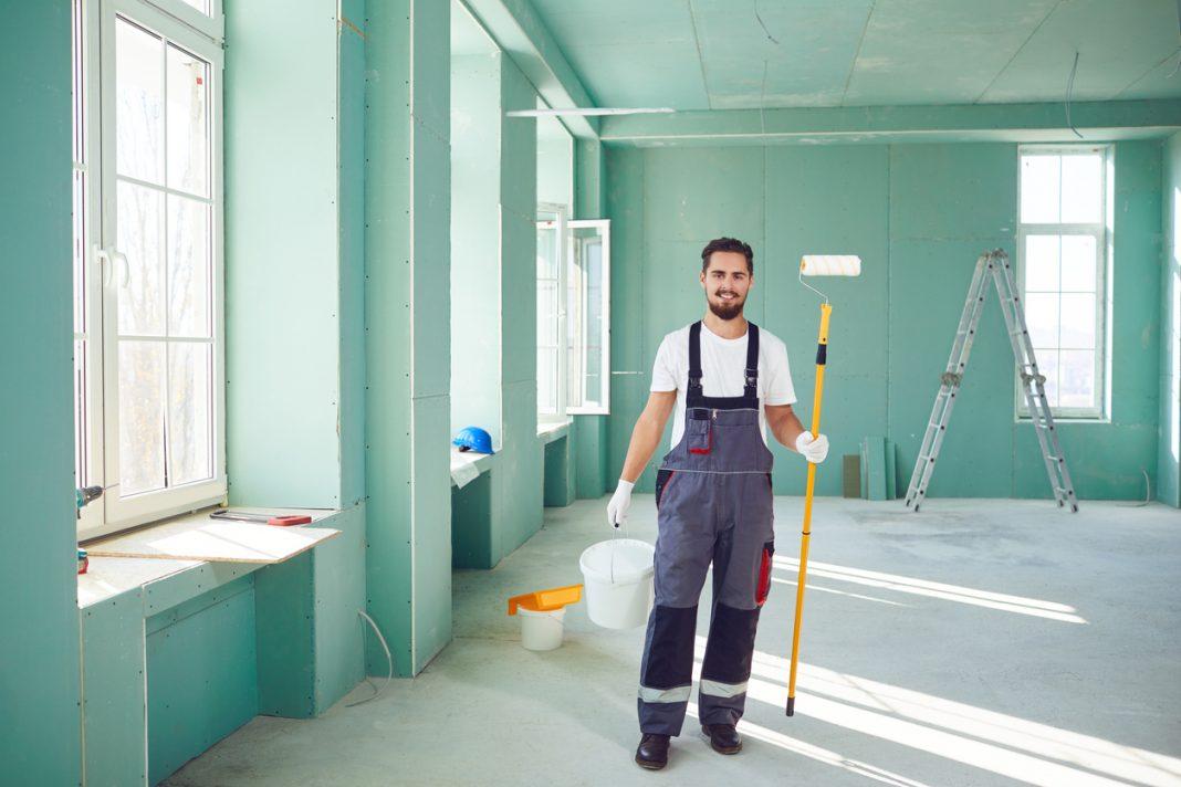 Un homme souriant avec son rouleau pour peindre les murs