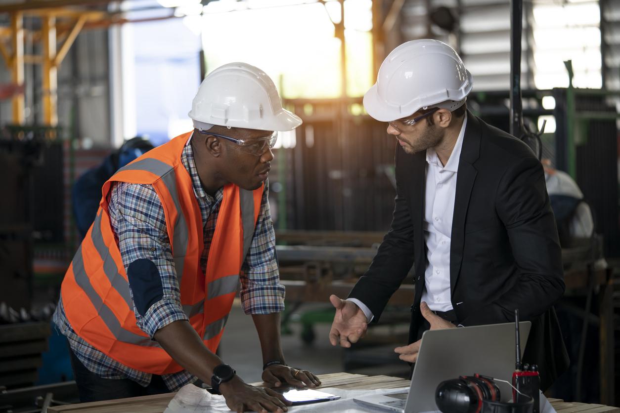 Deux hommes sur un chantier de construction entrain de discuter