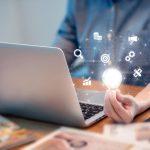 Une homme sur son ordinateur avec une ampoule dans les mains pour illustrer ses idées