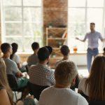 Des personnes assises entrain d'écouter un homme exerçant une conférence