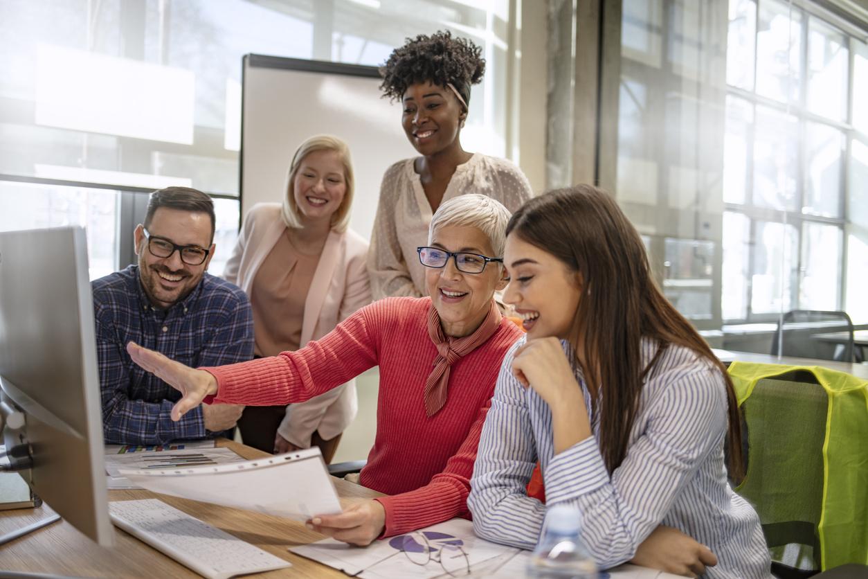 Des personnes souriantes en formation avec une dame devant un ordinateur