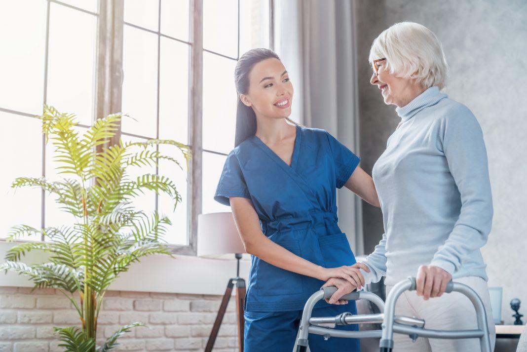 Une infirmière aidant une personne agée