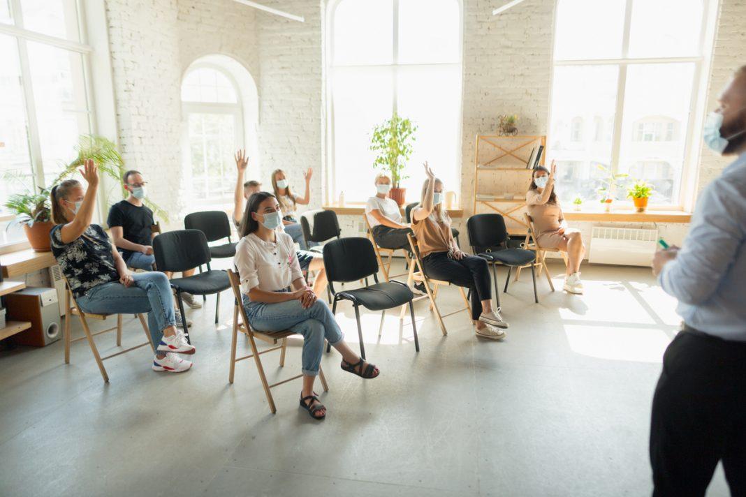 Des personnes assises dans une salle entrain d'écouter une conférence