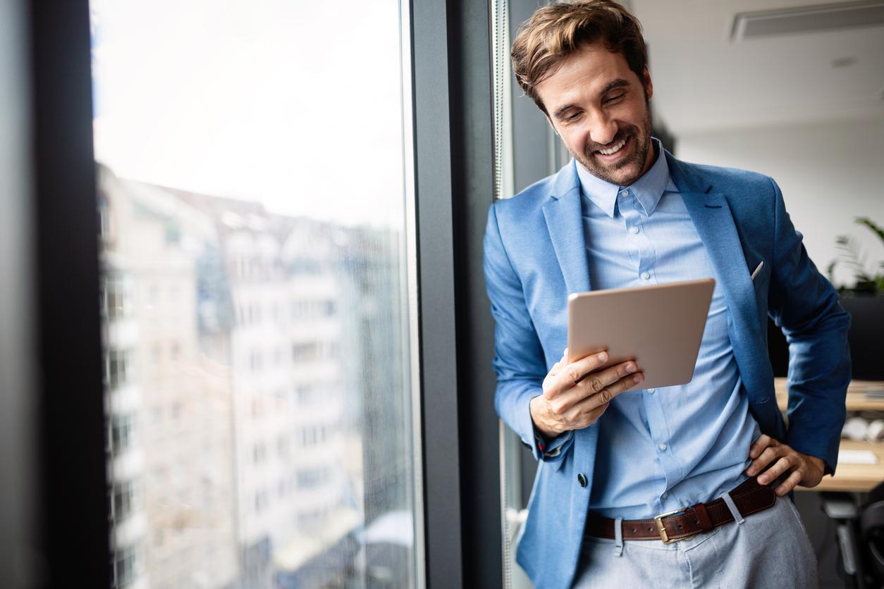 Un homme souriant avec un cahier à la main