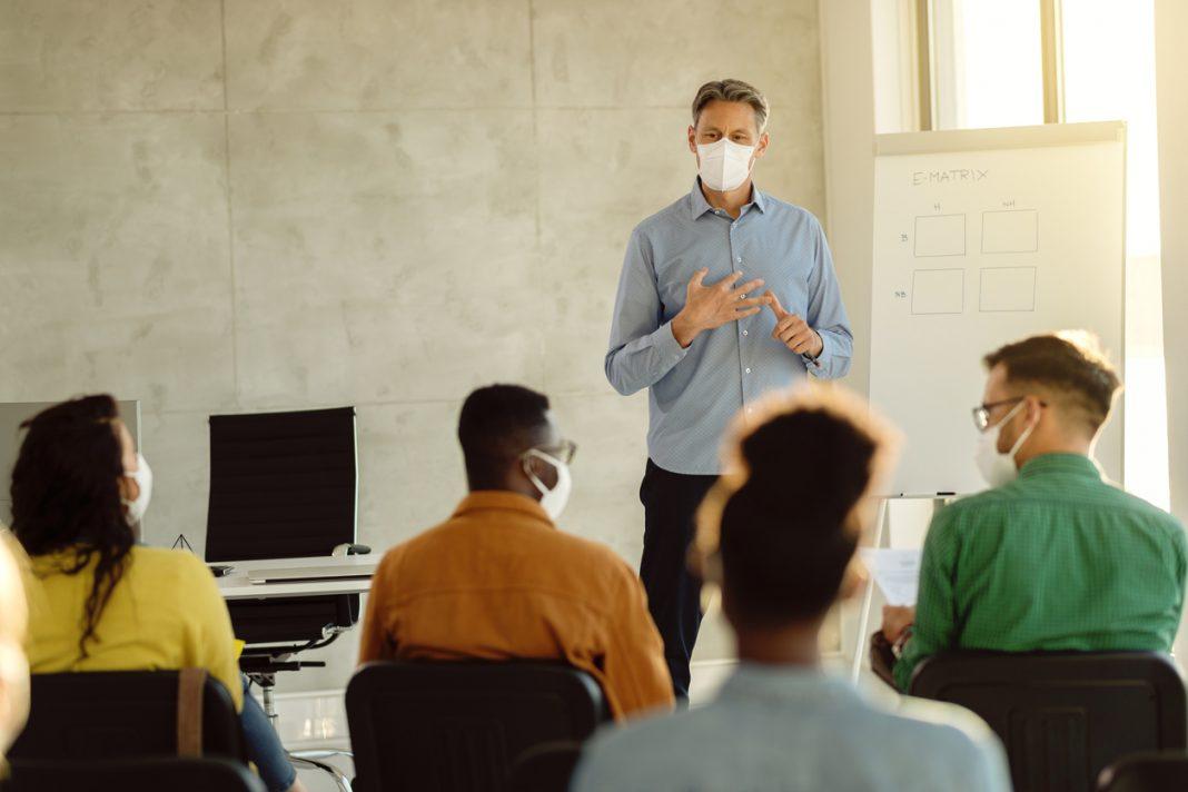 Un intervenant avec un masque entrain de donner un cours