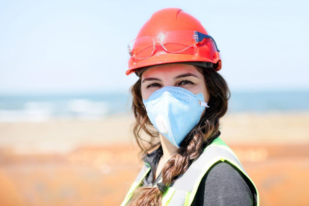 Une femme avec un casque pour faire des travaux et un masque