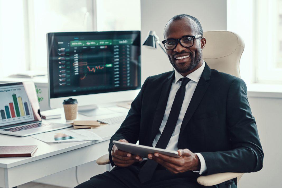un homme souriant avec des chiffres de trading sur son ordinateur
