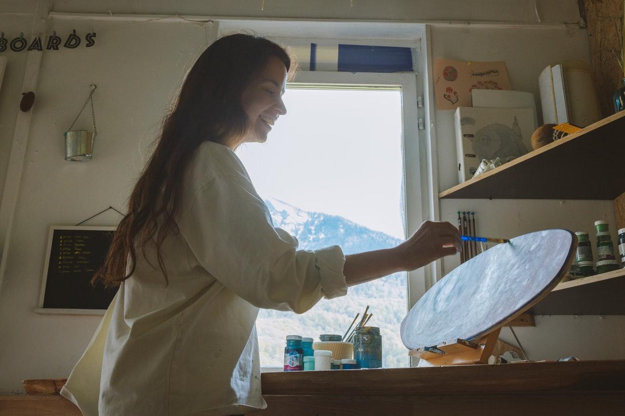 femme au multipotentiel peint sur canvas dans atelier peinture bleue