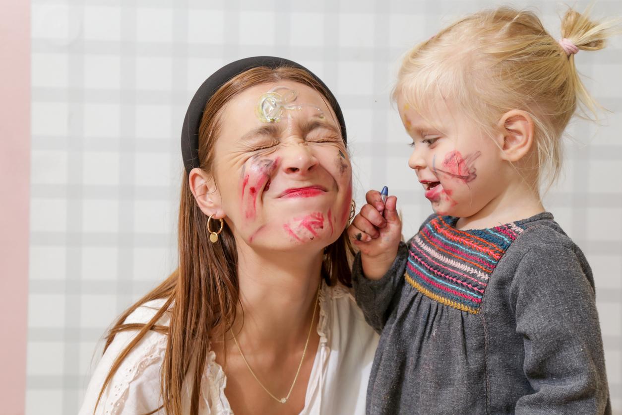 enfant dessine sur visage d'une femme