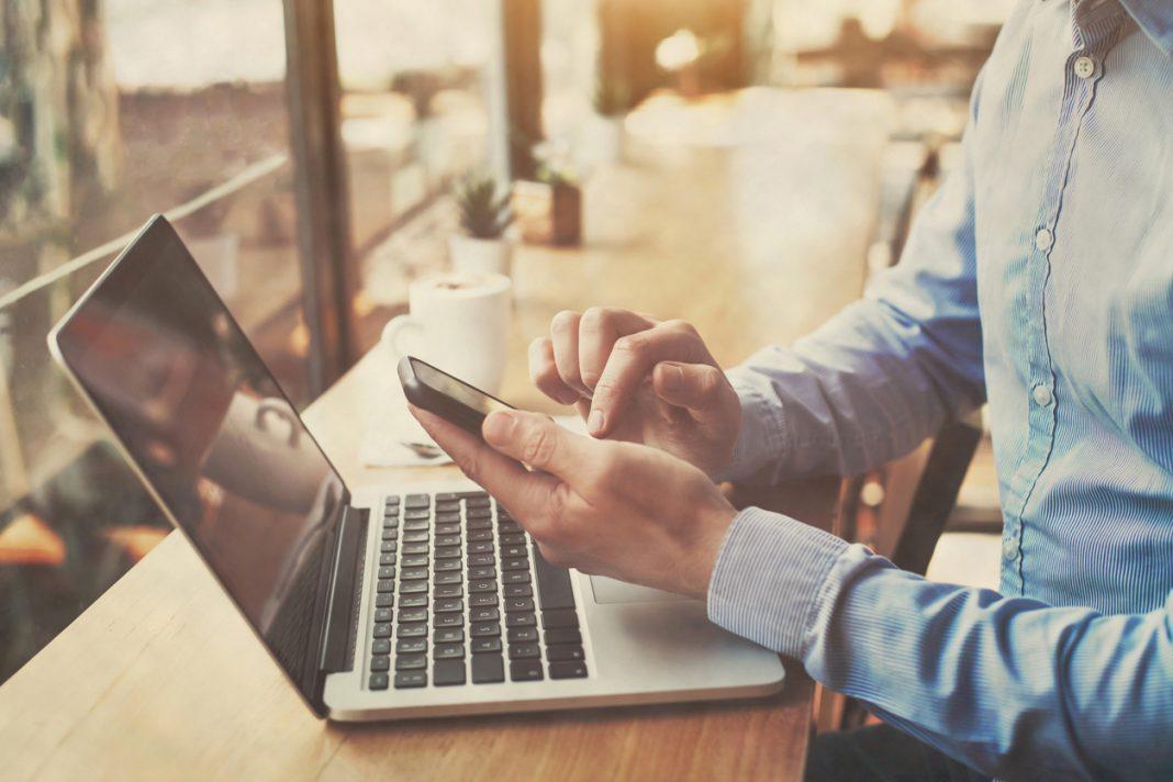 homme sur ordinateur et téléphone travail